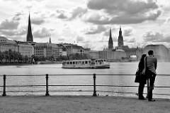Blick über die Binnenalster zum Ballindamm in der Hamburger Altstadt - Kirchtürme der St. Petrikirche, Nikolaikirche / Rathausturm. Ein Paar steht am Geländer der Alster, ein Alsterdampfer, Alsterschiff fährt Richtung Lombardsbrücke.