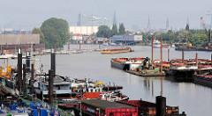 Arbeitsschiffe im Travehafen in Hamburg Steinwerder; ein Schubschiff mit Leichter fährt ein. Im Hintergrund das Polizeigebäude vom Wasserschutzpolizeikommissariat 2, Kirchtürme der Stadt + die Elbphilharmonie.