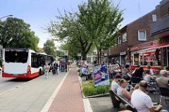 Busstation an der Neugrabener Bahnhofsstraße in Hamburg Neugraben-Fischbek; haltender Bus - Ladenzeile.