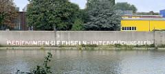 Regierungen wechseln - Unterdrückung bleibt; alter Schriftzug an einer Kaimauer am Rosskanal im Hamburger Hafen.