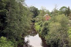Holzhaus, Wohnhaus zwischen Bäumen am Fluss Brasla in Straupe / Lettland.