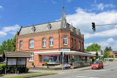 Backsteingebäude mit Schieferdach, Dachgauben und Erkerturm - moderne Ladenzeile; Lüneburger Straße in Stelle.