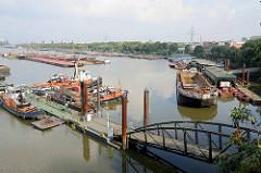 Übersicht / Panorama vom Travehafen in der Hansestadt Hamburg - eine Wassertreppe führt zu einem Ponton mit Arbeitsschiffen - eine Schute liegt an einer Werftanlage.