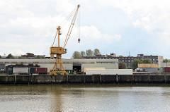 Gewerbebetrieb - Kran am Kai des Saalehafens im Hamburg Kleiner Grasbrook; im Hintergrund Wohnhäuser auf der Veddel.
