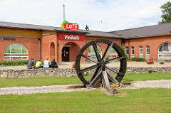 Dekor Wasserrad, Mühlenrad vor einem Supermarkt in Straupe, Lettland.