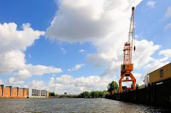 Blick in den Saalehafen im Hamburger Hafenstadtteil Kleiner Grasbrook; re. Kaianlage mit Kran und Container-Lastzug - re. Speichergebäude und Parkhaus am Dessauer Ufer.