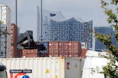 Containerlager und Lastwagen auf dem Gelände der UNIKAI Lagerei- und Speditionsgesellschaft in Hamburg Kleiner Grasbrook - im Hintergrund das Gebäude der Elbphilharmonie.