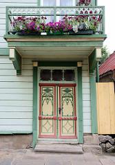 Alte Holztür mit farblich abgesetztem Schitzdekor - Holzbalkon mit Geranien, Holzhaus - historische Architektur in Fellin / Viljandi, Estland.