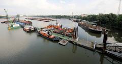 Schlepper und Arbeitsschiffe an einem langen Ponton im Travehafen von Hamburg Steinwerder.