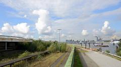 Blick vom Holthusenkai über die Elbe zur Hamburger Hafencity - lks. überwucherte Bahngleise und Verladeanlage / überdachte Rampe vom Überseezentrum.
