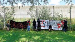 Solidaritäts-Demonstration vom S-Bahnhof Billwerder zu den No-G20 Gefangenen in der JVA Hamburg-Billwerder am 03.09.2017 . Transparente werden am Gefängniszaun aufgehängt, dahinter die Gefängnismauer.