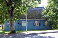 Holzhütte  mit Reetdach und blauer Holzfassade mit Fensterluken in Nida auf der Kurischen Nehrung in Litauen.