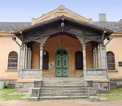 Hauseingang mit Holzsäulen und Schnitzdekor;  farbige, grüne Eingangstür - historische Architektur in Fellin / Viljandi, Estland.
