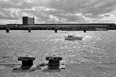 Blick vom Kirchenpauerkai über die Norderelbe zum Hamburger Stadtteil Kleiner Grasbrook. Ein Sportboot fährt elbabwärts, ein Schubschiff mit Schute Richtung Elbbrücken. Dahinter die leerstehenden Lagerhäuser / Verwaltungsgebäude vom Überseezentrum.