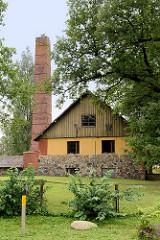 Wohnhaus mit Feldsteinmauer - hoher Schornstein mit Storchennest in Straupe.