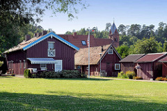 Holzhäuser und Holzschuppen in Juodkrantė auf der Kurischen Nehrung - im Hintergrund der Kirchturm der ev. Kirche; neogotischer Baustil - eingeweiht 1885.