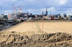 Das Baugelände am Versmannkai beim Hamburger Baakenhafen wird mit Sand aufgeschüttet, um die Gebäude gegen Hochwasser zu schützen. Im Hintergrund Baustellen an der Baakenhafen Brücke.