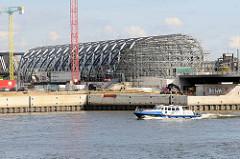 Blick über die Norderelbe zum Kirchenpauerkai und der Baustelle / Stahlkonstruktion vom Bahnhof Elbbrücken; ein Polizeiboot fährt Patrouille.