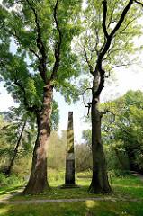 Obelisk am Heckenrosenweg in Hamburg Lokstedt, hohe Eichen. Jakob von Axen erwarb 1786 den Kollauhof und baute ihn zu einem der Zentren des gesellschaftlichen Lebens in Hamburg aus. Stichkanäle umgaben das Herrenhaus wie eine Wasserfestung.