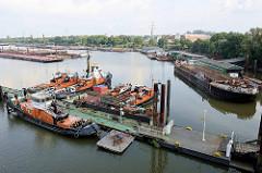 Übersicht vom Travehafen in der Hansestadt Hamburg - eine Wassertreppe führt zu einem Ponton mit Arbeitsschiffen - eine Schute liegt an einer Werftanlage.