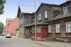Historische Architektur in Fellin / Viljandi, Estland; alte Häuser mit Veranda, rohe Holzfassade, Fundament mit Findlingen - im Hintergrund restaurierte, neue Wohnhäuser.