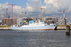Kulturschiff Stubnitz an seinem Liegeplatz Kirchenpauerkai, dahinter Baustellen mit Baukränen am Baakenhafen.