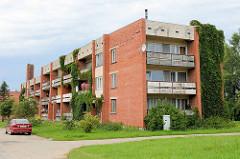 Schlichtes Wohngebäude, Wohnblock mit Balkons und mit Efeu bewachsener Hausfassade in Straupe.