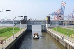 Rugenberger Schleuse in Hamburg Waltershof; das Schleusentor öffnet sich, eine Barkasse fährt in den Rugenberger Hafen ein.