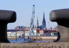 Blick durch zwei Eisenpollern am Baakenwerder auf den Hafenkran, U 434 im Baakenhafen; im Hintergrund die Kirchtürme der Hamburger St. Katharinen und Nikolaikirche. (2006)