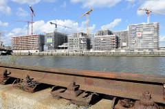 Blick zu der Baustelle am Versmannkai im Hamburger Baakenhafen; im Vordergrund die alte Laufschiene eines Hafenkrans am Petersenkai.