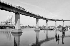Betonpfeiler / Stelzen der Auffahrt Köhlbrandbrücke über den Rugenberger Hafen in Hamburg Waltershof; im Hintergrund die Autobahn A7 und Containerkräne vom Terminal Eurogate.