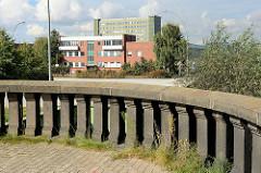 Ausblick von den Hamburger Freihafen-Elbbrücken zum Areal des ehem. Übersee-Zentrum auf dem Kleinen Grasbrook; im Vordergrund eine Steinbalustrade / Geländer bei der Freihafen Elbbrücke.