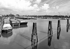 Blick über den Travehafen - einem der vielen Hafenbecken im Hamburger Hafen; alte Holzdalben ragen aus dem Wasser - Schuten / Leichter liegen an einem Ponton.