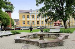 Rathausplatz / Marktplatz mit Brunnen in Fellin / Viljandi, Estland; Gebäude der Stadtverwaltung, lks. der historische Wasserturm.