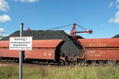 Förderanlage und offen Güterwagen - Schüttgutwaggons am Sandauhafen in Hamburg Altenwerder. Schild - Hinweis: Achtung Funkferngesteuerter Rangierbetrieb. Überschreiten der Gleise verboten.