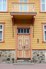 Alte Holztür mit Holzbalkon, ockerfarbenes Holzhaus - historische Architektur in Fellin / Viljandi, Estland.
