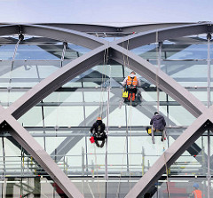 Handwerker / Industriekletterer arbeiten an der Verglasung vom Dach der Haltestelle Elbbrücken in der Hamburger Hafencity.