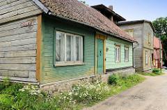 Holzhäuser mit teilweise farbig gestricherner Fassade - blühende Kamille an der Strasse; historische Architektur in Fellin / Viljandi, Estland.