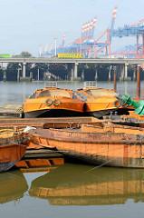 Arbeitsschiffe Schuten im Rugenberger Hafen von Hamburg Waltershof - im Hintergrund die Autobahn A7 und Containerkräne.