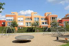 Neubaugebiet an der Emil Andresen Strasse in Hambug Lokstedt - moderne Engergieeffizenzhäuser mit farbiger Fassade - Spielplatz mit Sand und Metall Spielgeräten.