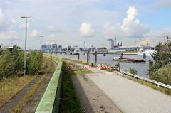 Ausblick vom Holthusenkai über die Elbe zur Hamburger Hafencity - ein Schubverband fährt elbaufwärts.