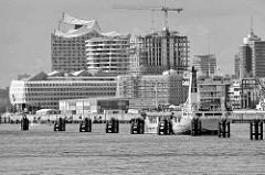 Moderne Architektur in der Hamburger Hafencity - Blick zum Strandkai und dem Kreuzfahrtschiff Terminal - im Vordergrund hat ein Frachter an den Dalben in der Elbe festgemacht.