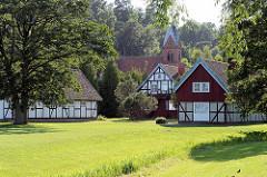 Holzhäuser / Fachwerkgebäude in Juodkrantė auf der Kurischen Nehrung - im Hintergrund der Kirchturm der ev. Kirche; neogotischer Baustil - eingeweiht 1885.