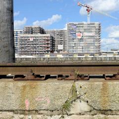 Blick zu den Baustellen am Versmannkai im Hamburger Baakenhafen; im Vordergrund Streichdalben und alte Laufschiene eines Hafenkrans am Petersenkai.