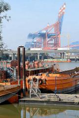 Arbeitsschiffe,  Schuten im Rugenberger Hafen von Hamburg Waltershof - im Hintergrund die Autobahn A7 und Containerkräne.