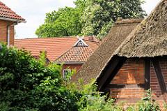 Hausdächer in Stelle - Reet u. Ziegel; Pferdeköpfe als Giebelschmuck.