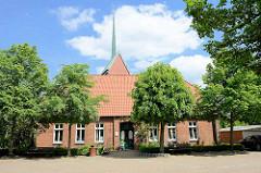 Gemeindebücherei von Stelle, vormals Lehrer-Wohnhaus + davor altes Schulgebäude - im Hintergrund der Kirchturm der St. Michaeliskirche.