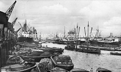 Altes Bild vom Kaiser-Wilhelm-Hafen in Hamburg - geschäftiges Treiben mit beladenen Schuten, Säcke,  Kisten, Ballen; Kräne und Dampfschiff am Kronprinzenkai - re. Frachtschiffe am Auguste Victoria Kai.