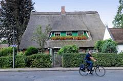 Wohnhaus mit Reetdach und Dachfenstern, blühende Geranien - Fischbeker Weg im Hamburger Stadtteil Neugraben-Fischbek.