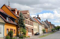 Wohnhäuser unterschiedlicher Baustile in der Pretzscher Straße von Dommitzsch - im Hintergrund der Kirchturm der St. Marienkirche und der Uhrenturm vom Dommitzscher Rathaus.